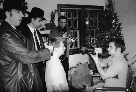 MERRY CHRISTMAS! cinematographer Kenny Gilbreath lines up a shot with actors (from left) John Dowers, Greg Trumbold, and Greg Wolf while James Schirmer looks on.